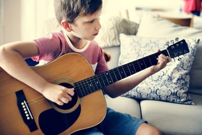 Niño sobre sillon tocando instrumento