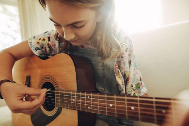 Niña aprendiendo guitarra