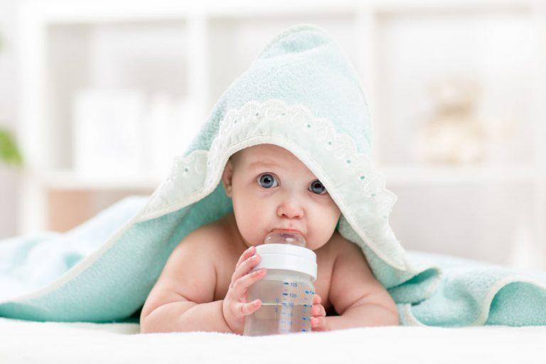 Bebé tomando agua de su biberón