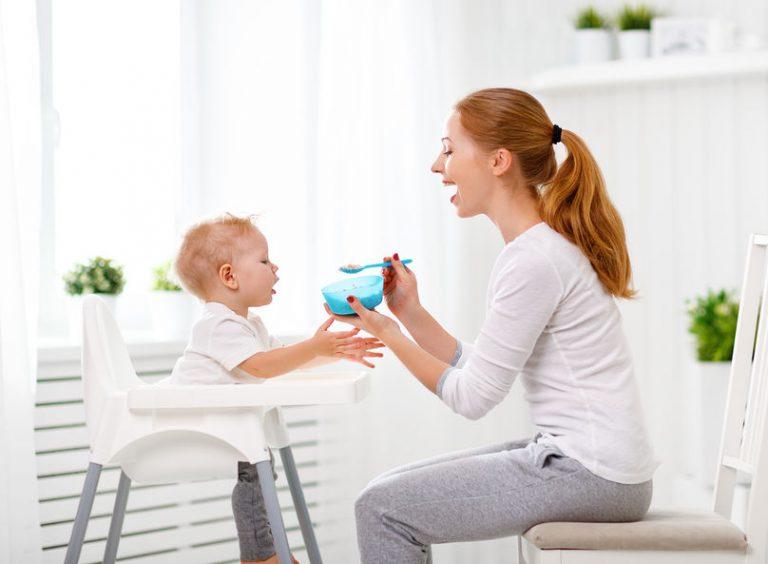 Una madre dando de comer a su bebé