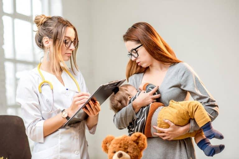 Pediatra en consulta con madre de familia y su bebé