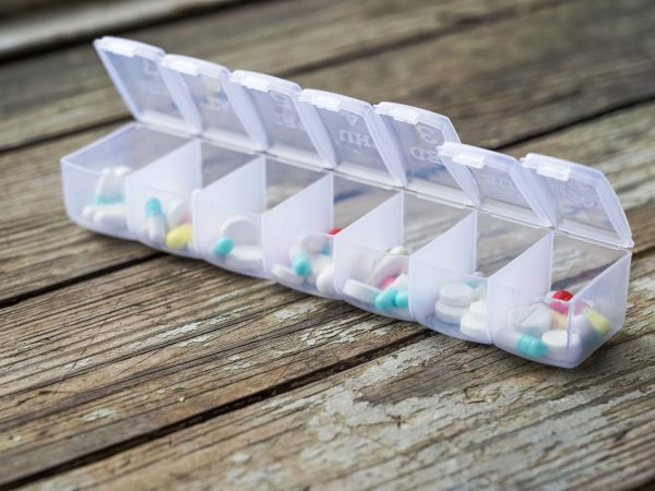 Variety of pills in white plastic pill organizer on weathered wood, free space for text