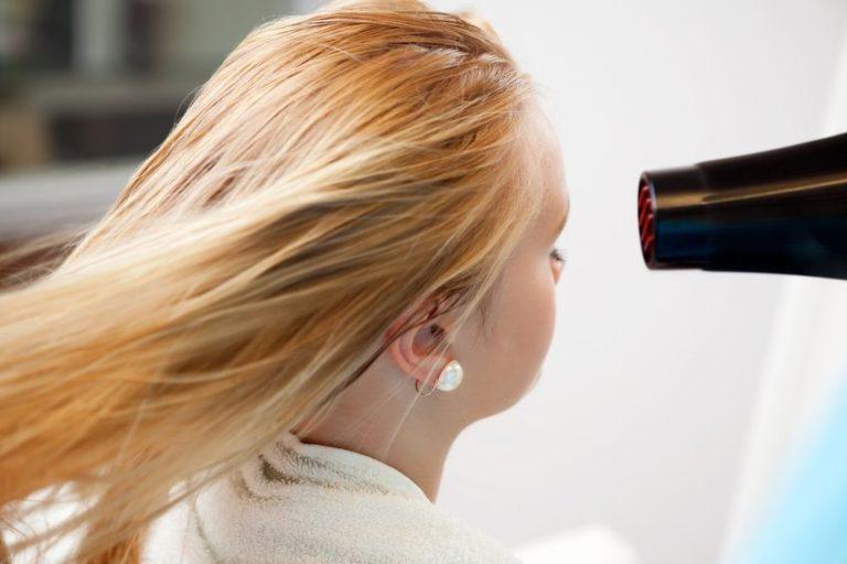 Mujer en sala de belleza secándose el cabello