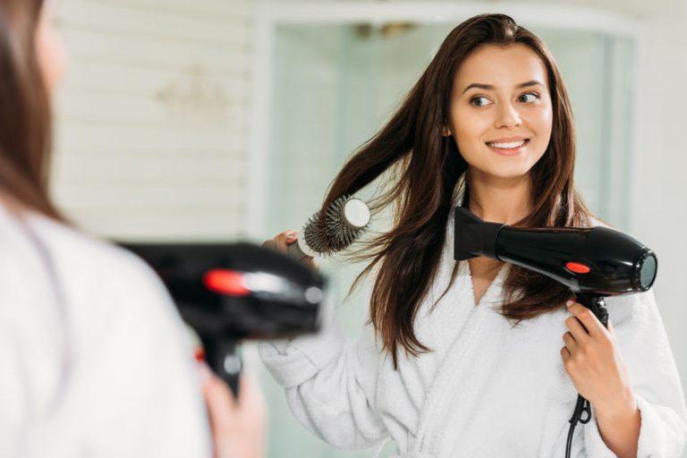 Mujer secadose el cabello con secador