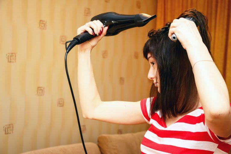 Mujer joven secándose el cabello