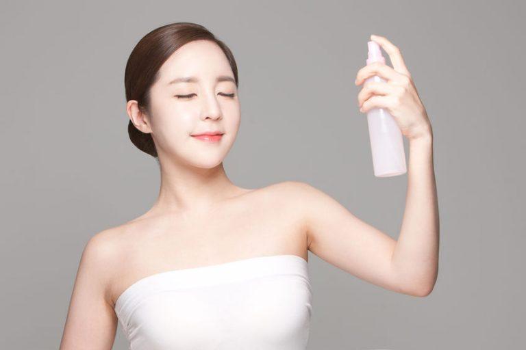 Mujer con spray de maquillaje