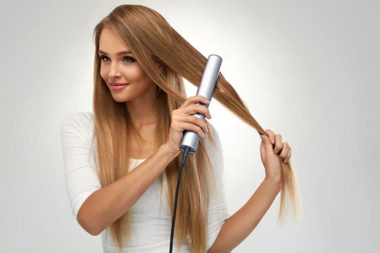 Una chica rubia alisándose el pelo