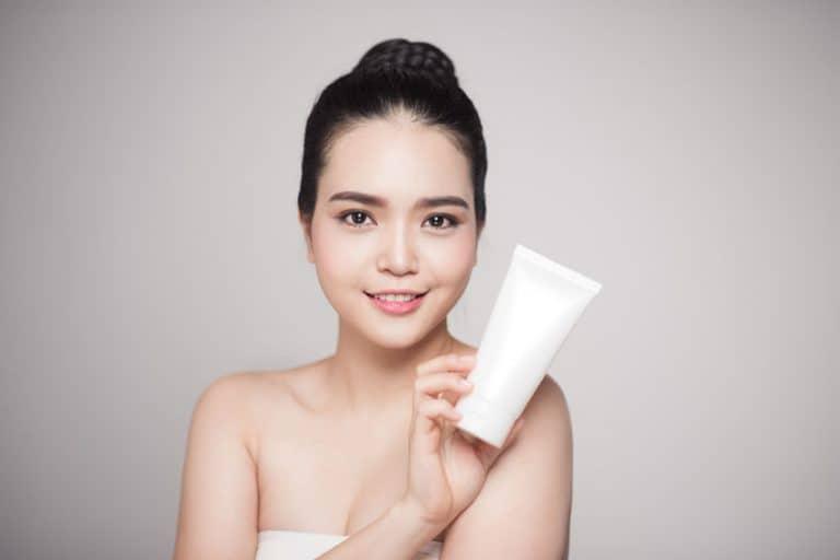 Mujer asiática con crema en manos