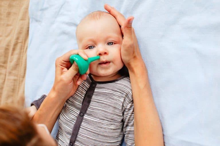 Niño con aspirador nasal verde