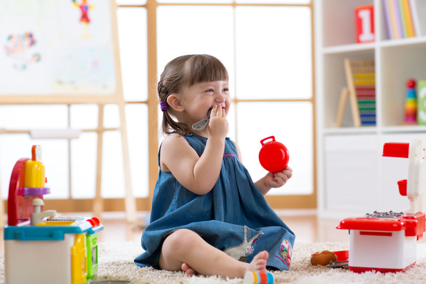 Pretty child girl playing with a toy kitchen in children room
