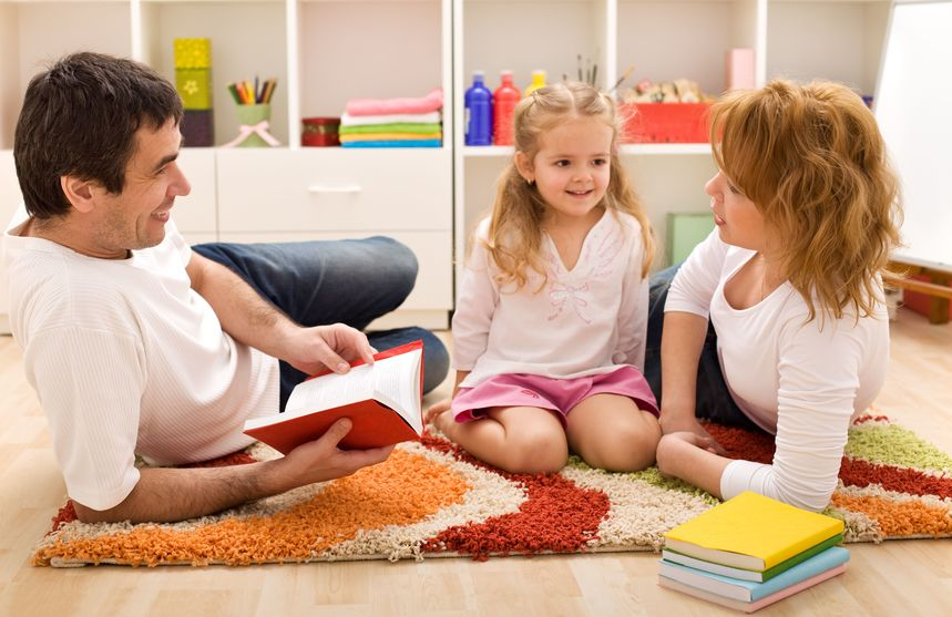 happy family reading a story laying on the floor in the kids room