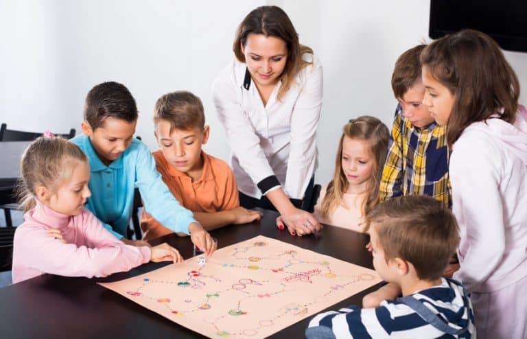 Mujer con niños jugando a un juego de mesa