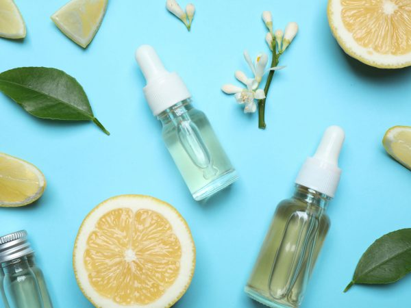 Flat lay composition with bottles of citrus essential oil on light blue background