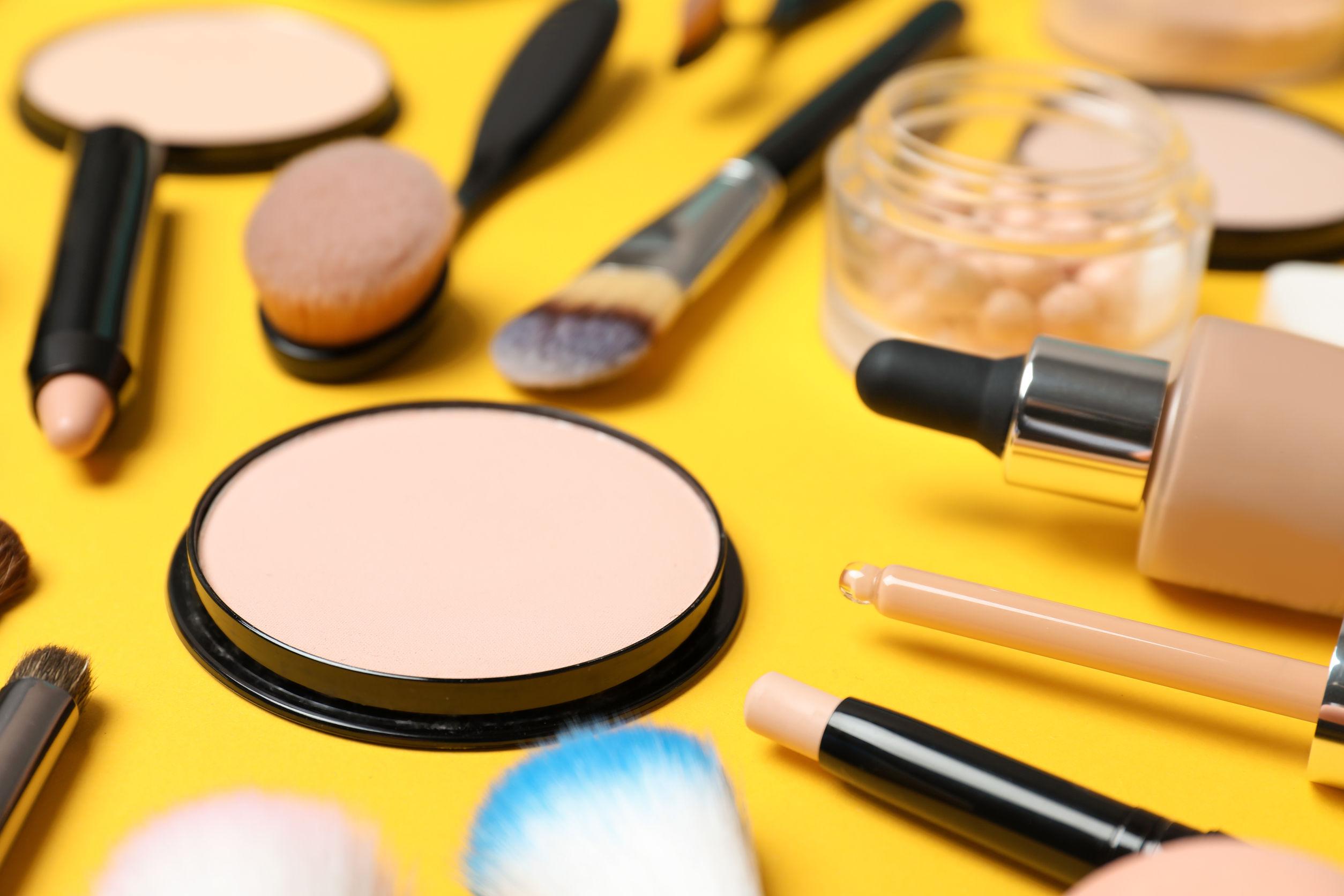 Varios accesorios de maquillaje sobre fondo amarillo