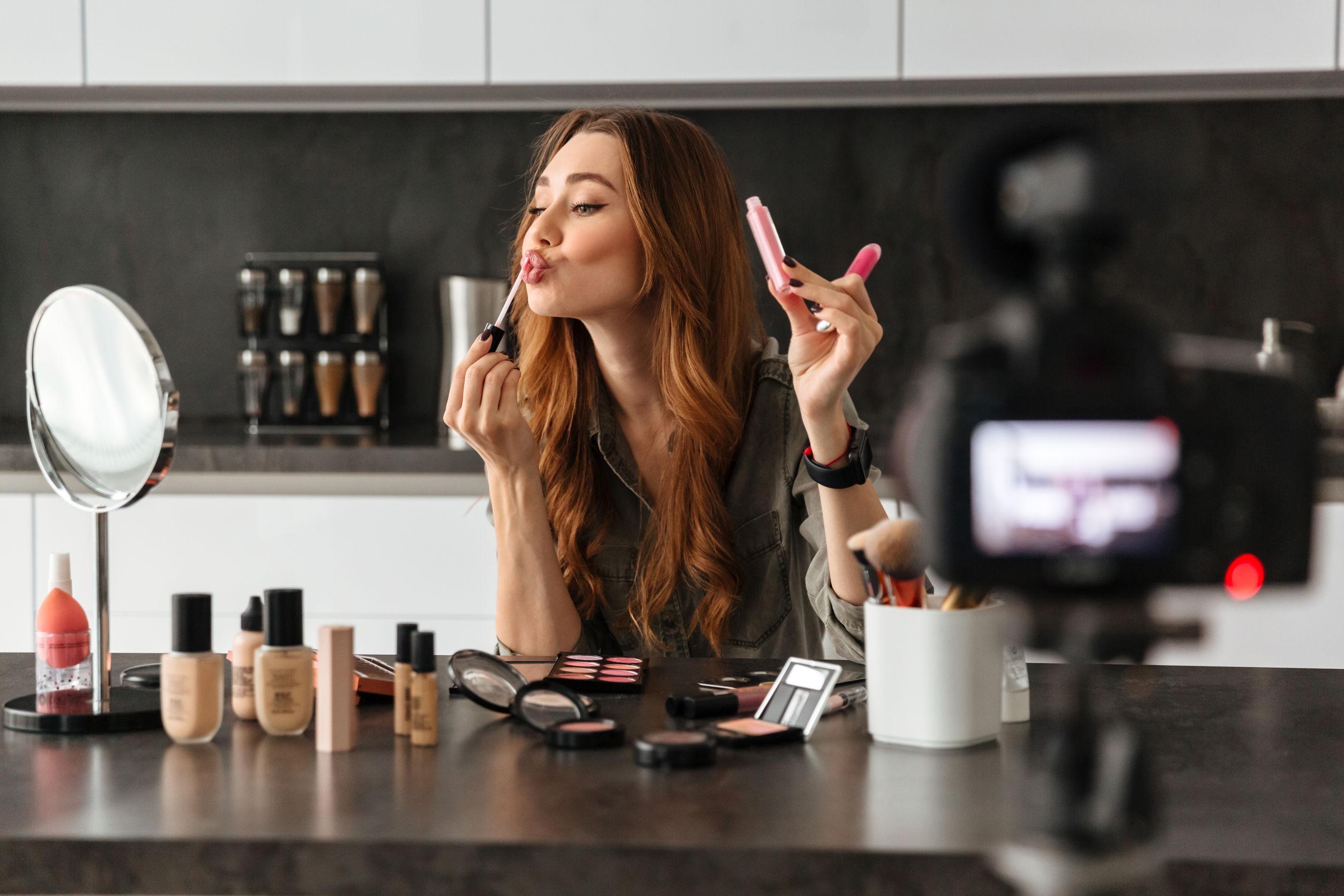 una niña saludable que graba su video episodio de blog sobre nuevos productos cosméticos