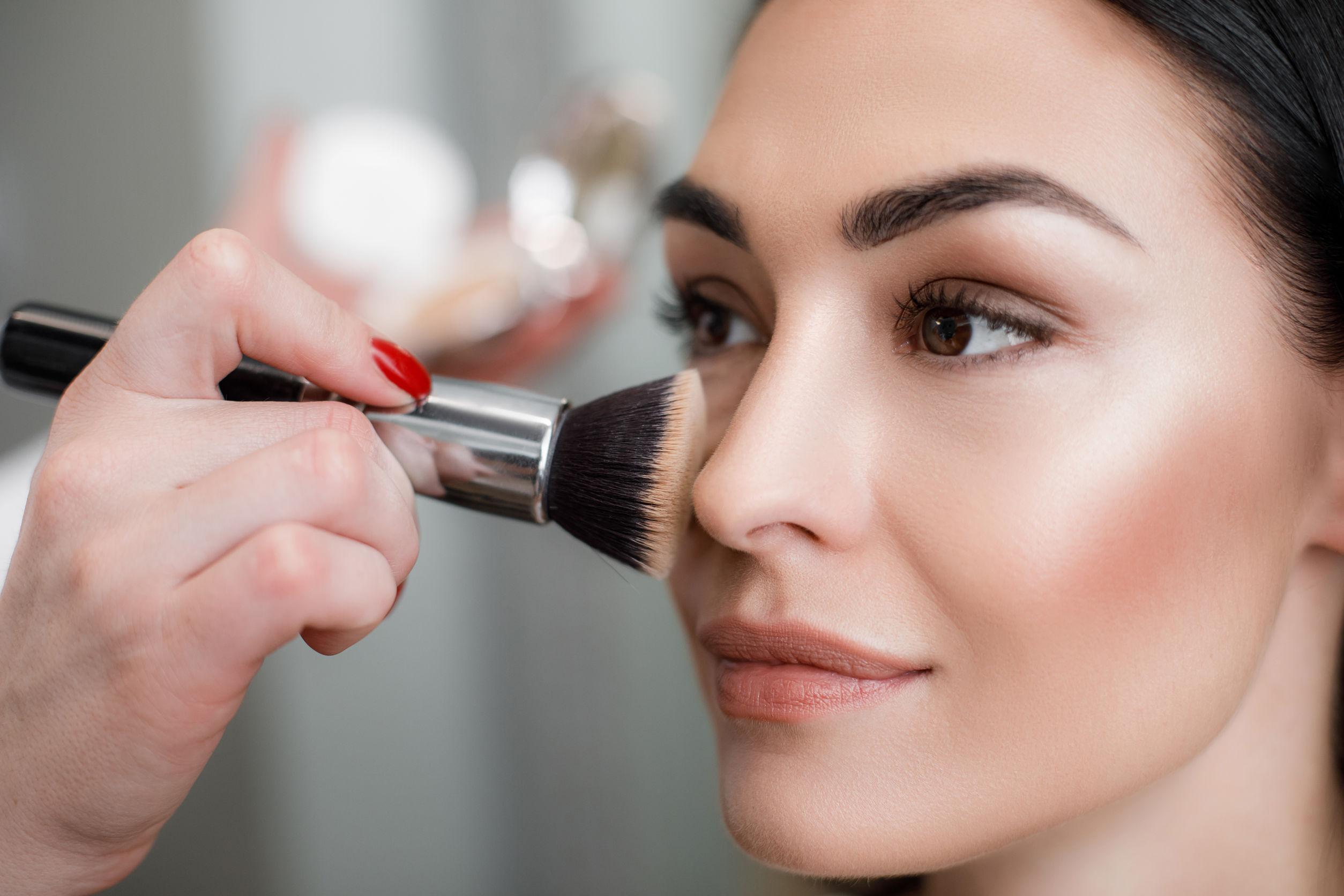 Una mujer siendo maquillada en la cara