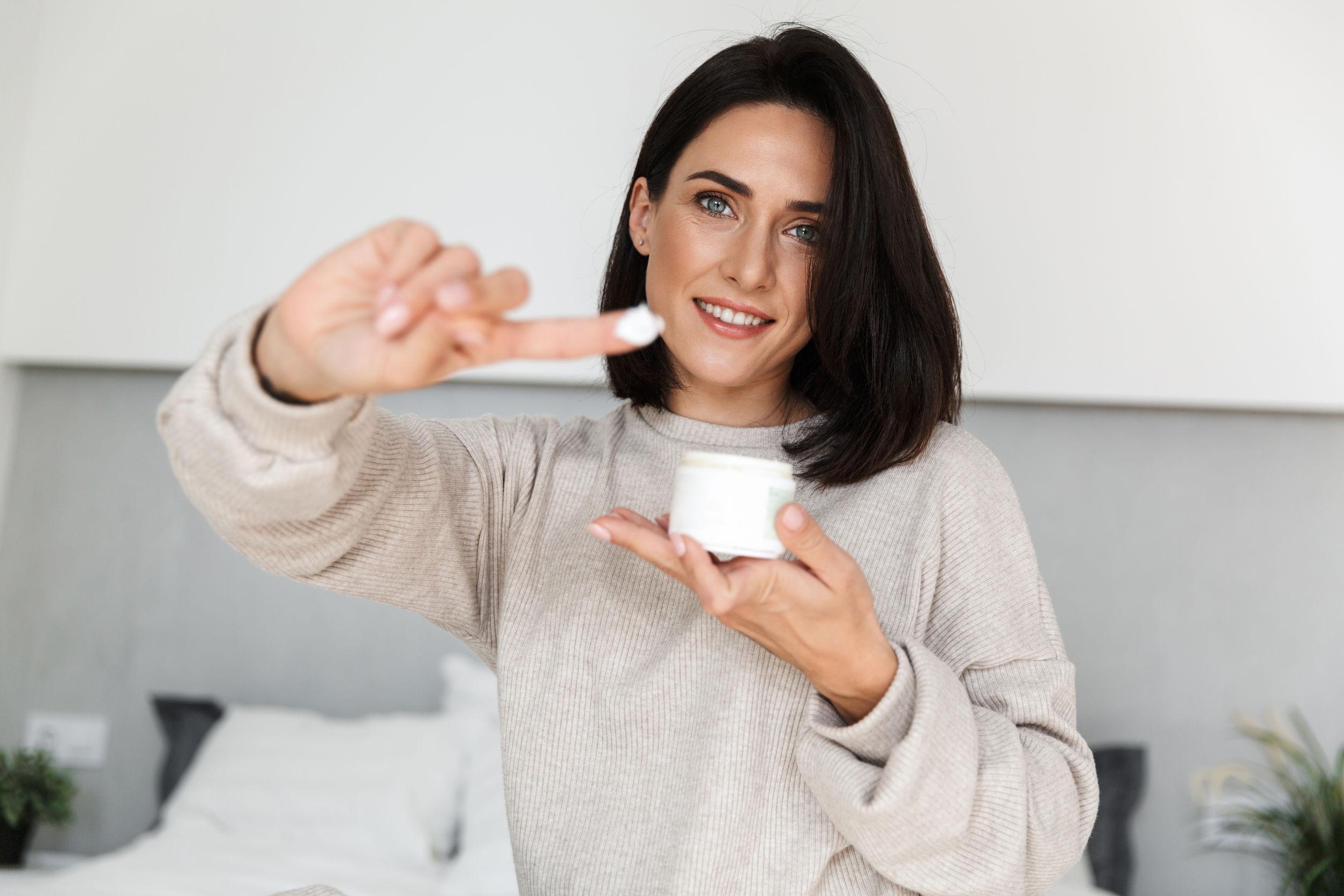 Imagen de mujer atractiva de 30 años sosteniendo el tarro con crema reafirmante