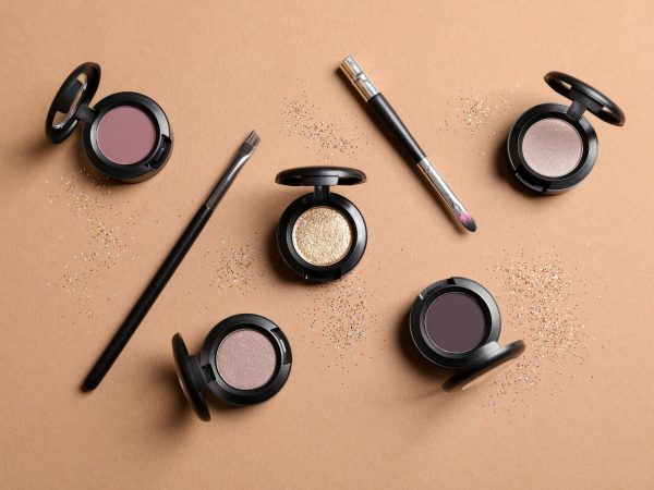 Flat lay composition with different eye shadows on color background