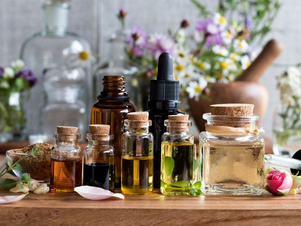 82809057 – selection of essential oils, with herbs and flowers in the background
