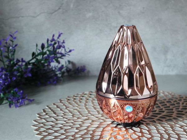 159300357 – luxury design rose gold colour aromatic humidifier diffuser machine display on the grey table in the living room during christmas new year party with happy family members