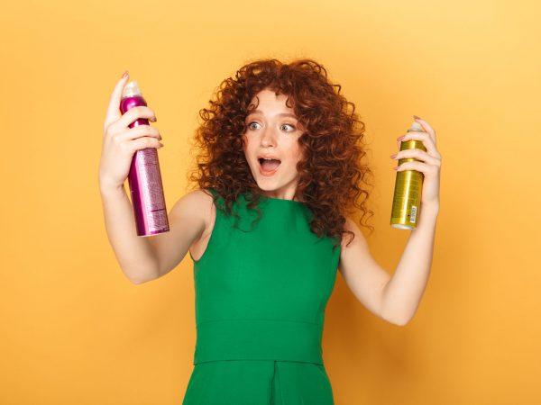 Mujer pelirroja rizada feliz sosteniendo dos aerosoles para el cabello sobre fondo amarillo
