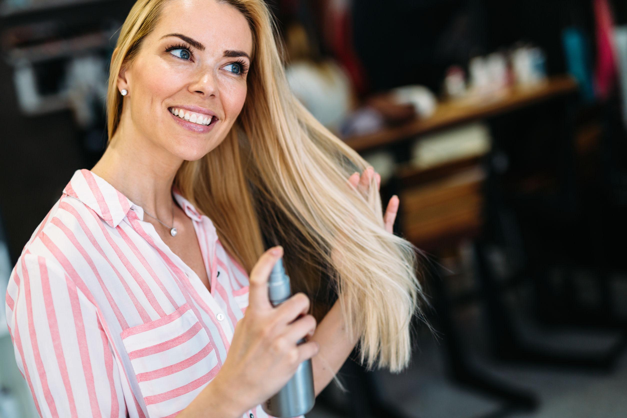 Retrato de mujer rubia hermosa joven sonriente alegre aplicandose champu seco