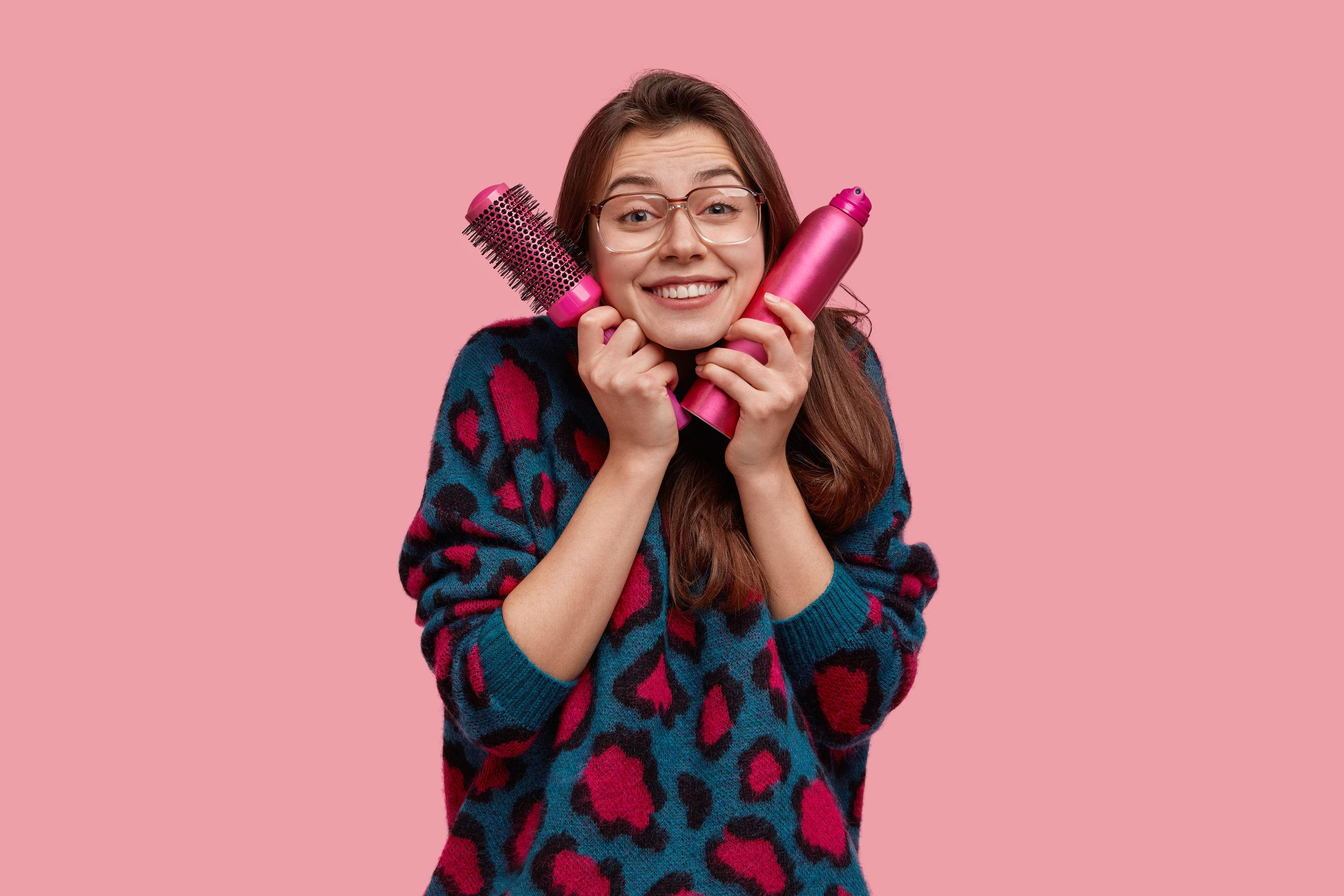 Mujer feliz con cepillo y champu seco en ambas manos en fondo rosado