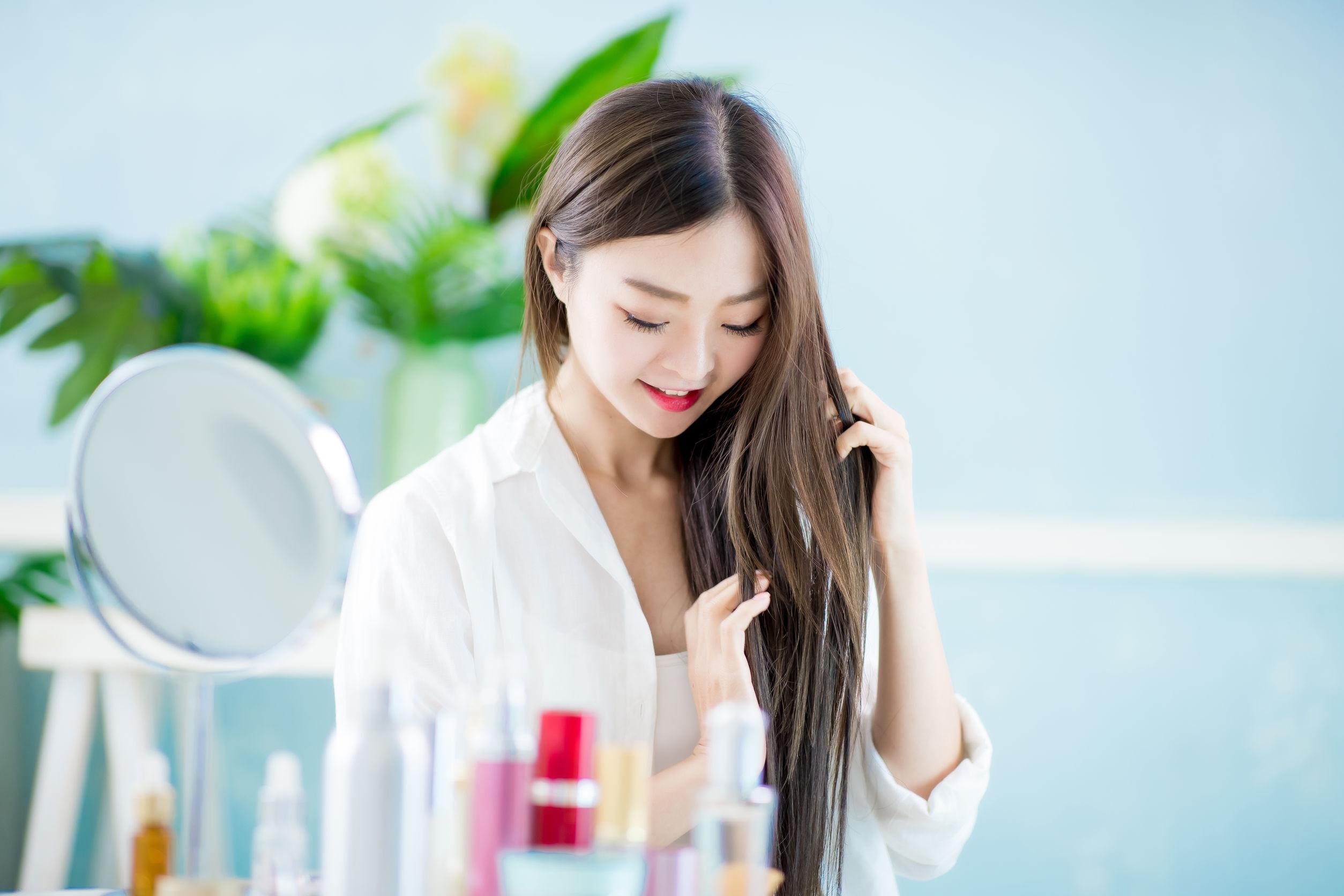 Hermosa mujer asiática aplicando champu seco en el cabello con espejo en casa