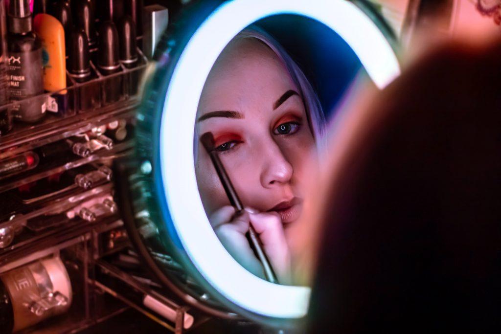 chica maquillandose en espejo con luz