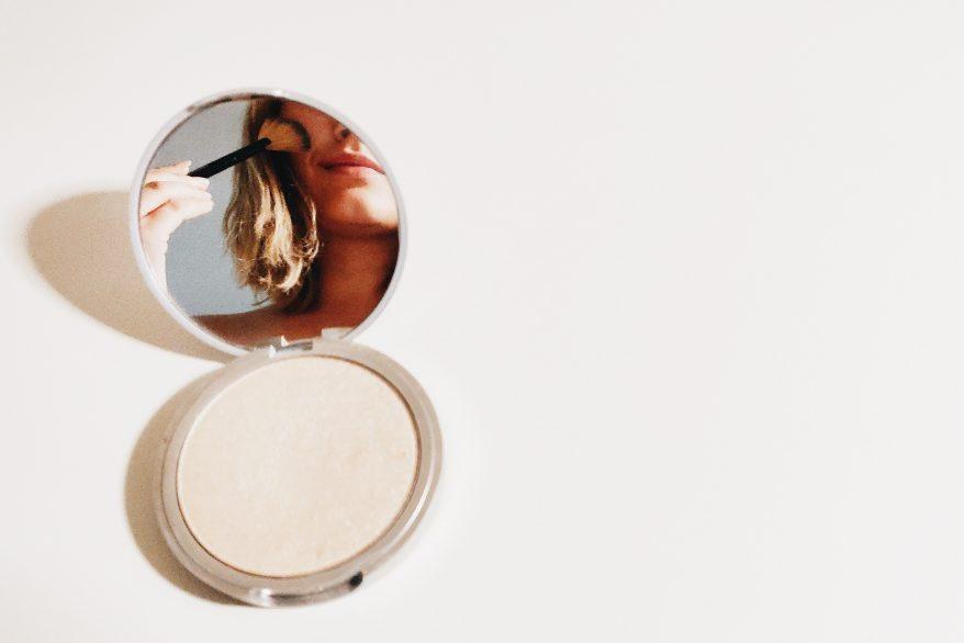 chica maquillandose en espejo de mano