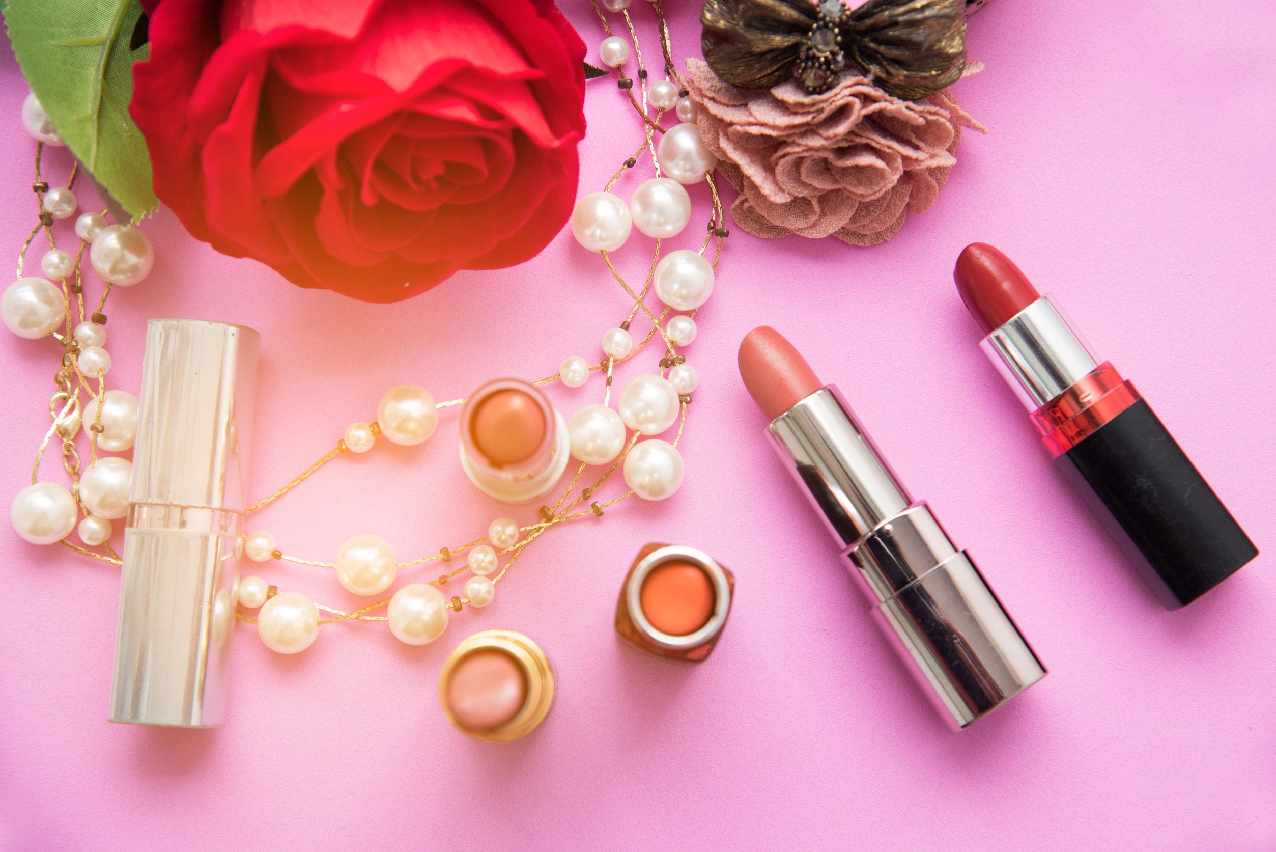Composición decorativa plana con lápiz labial de colores, perlas y flores