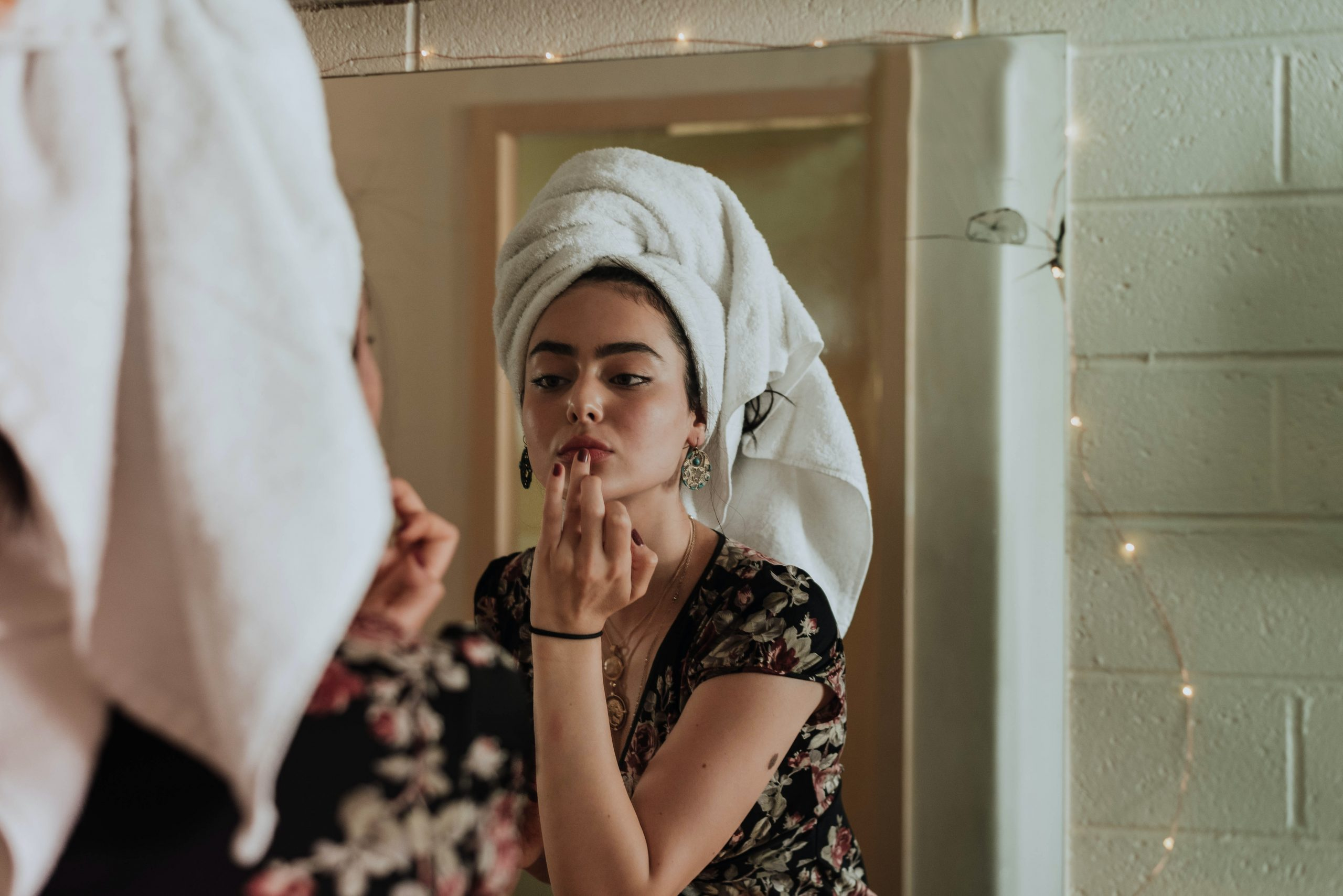Mujer joven frente al espejo aplicandose lapiz labial