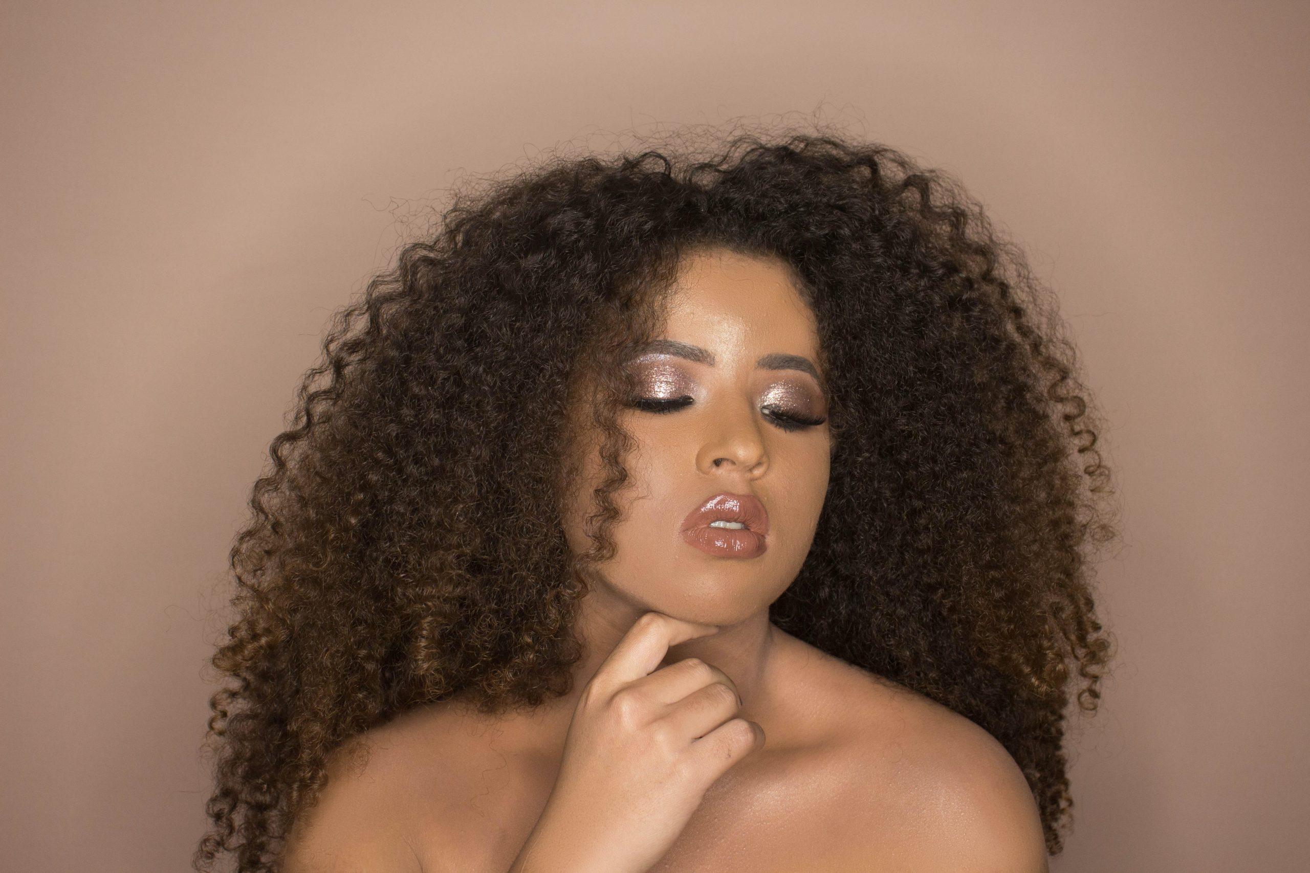 Mujer de cabello rizado luciendo maquillaje