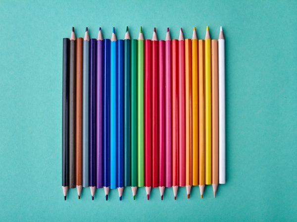 Row of multicolored pencils on color background. Set of colorful pencils on turquoise background. Concept of school supplies.