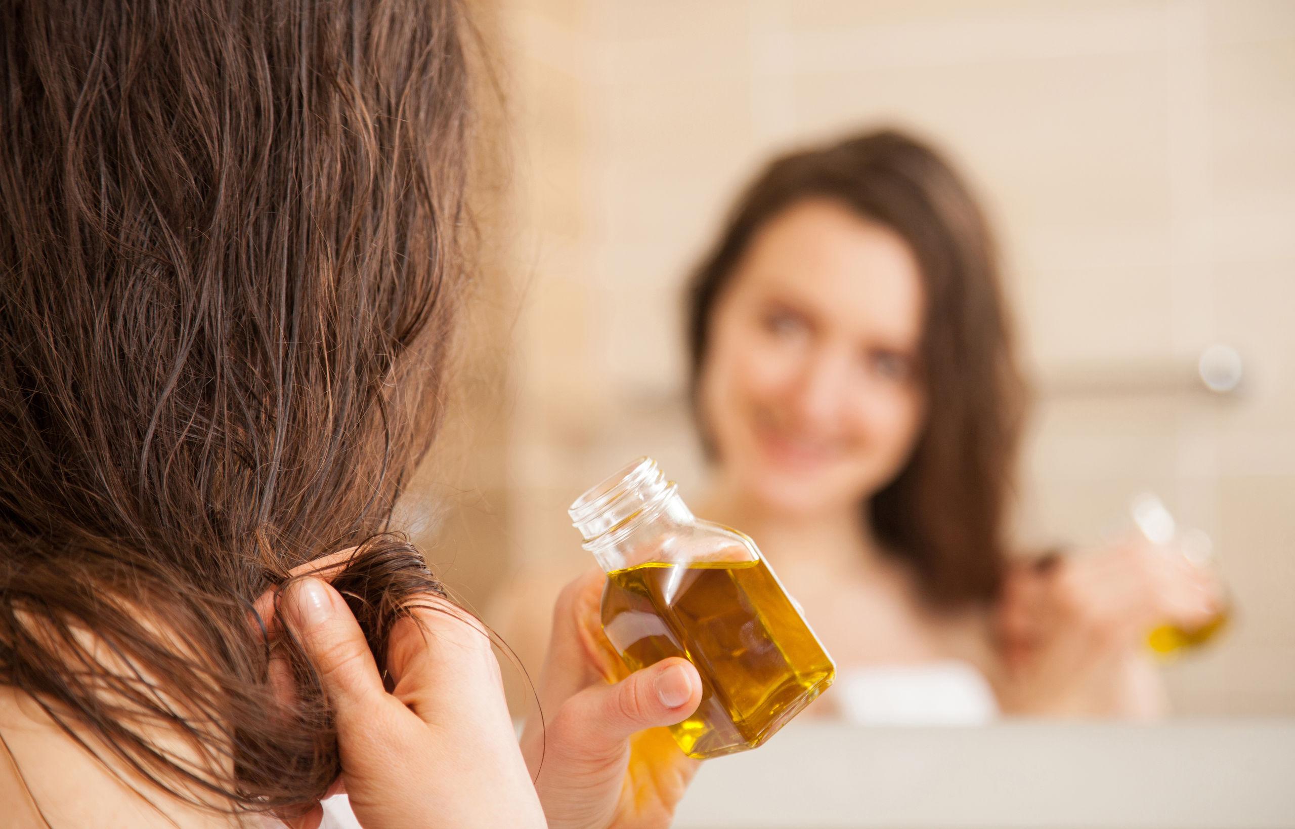 chica aplicando aceite para el cabello
