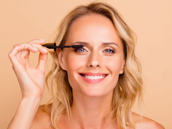 Close-up portrait of trendy modern nice cheery wavy-haired lady with perfect pure clean clear fresh smooth flawless shine skin applying mascara brush on eye lashes isolated on beige background.