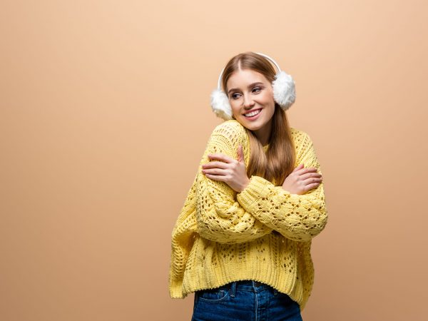 cold smiling woman in yellow sweater and ear warmers, isolated on beige