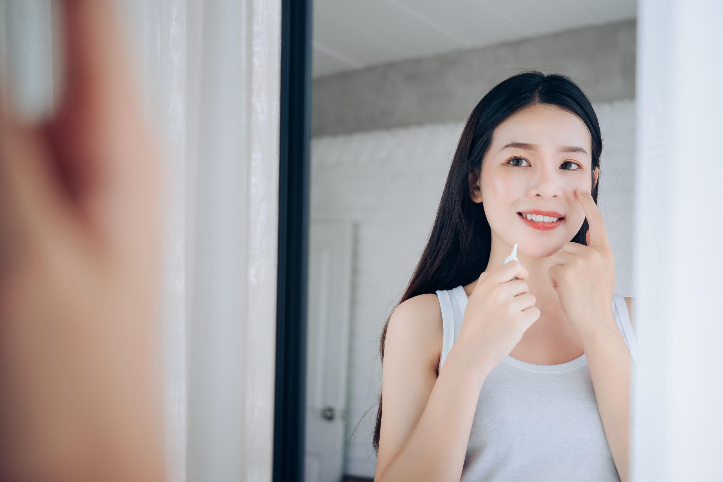 Mujer asiática de la belleza usa el cuidado de la piel del gel del acné después de limpiar en la cara su felicidad y mira el espejo en el dormitorio blanco.