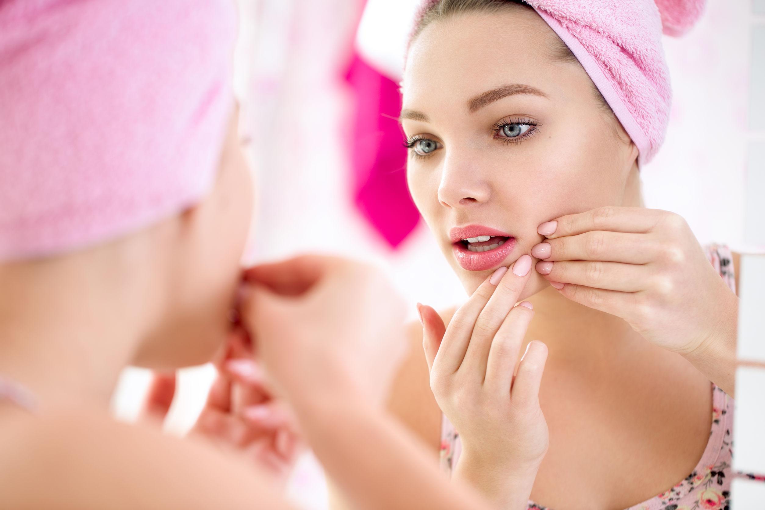 Joven adolescente busca grano en su rostro en un espejo
