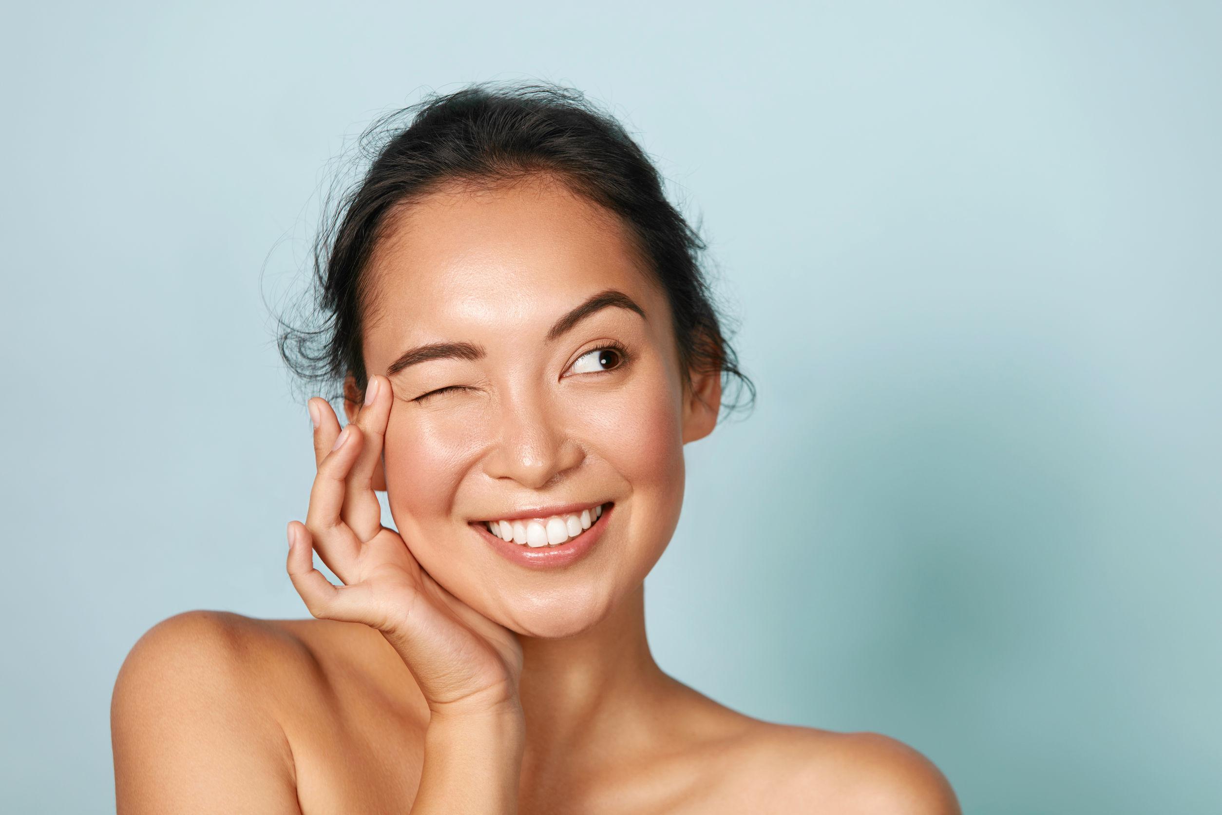 Hermosa chica asiática sonriente modelo con maquillaje natural tocando piel hidratada brillante sobre fondo azul