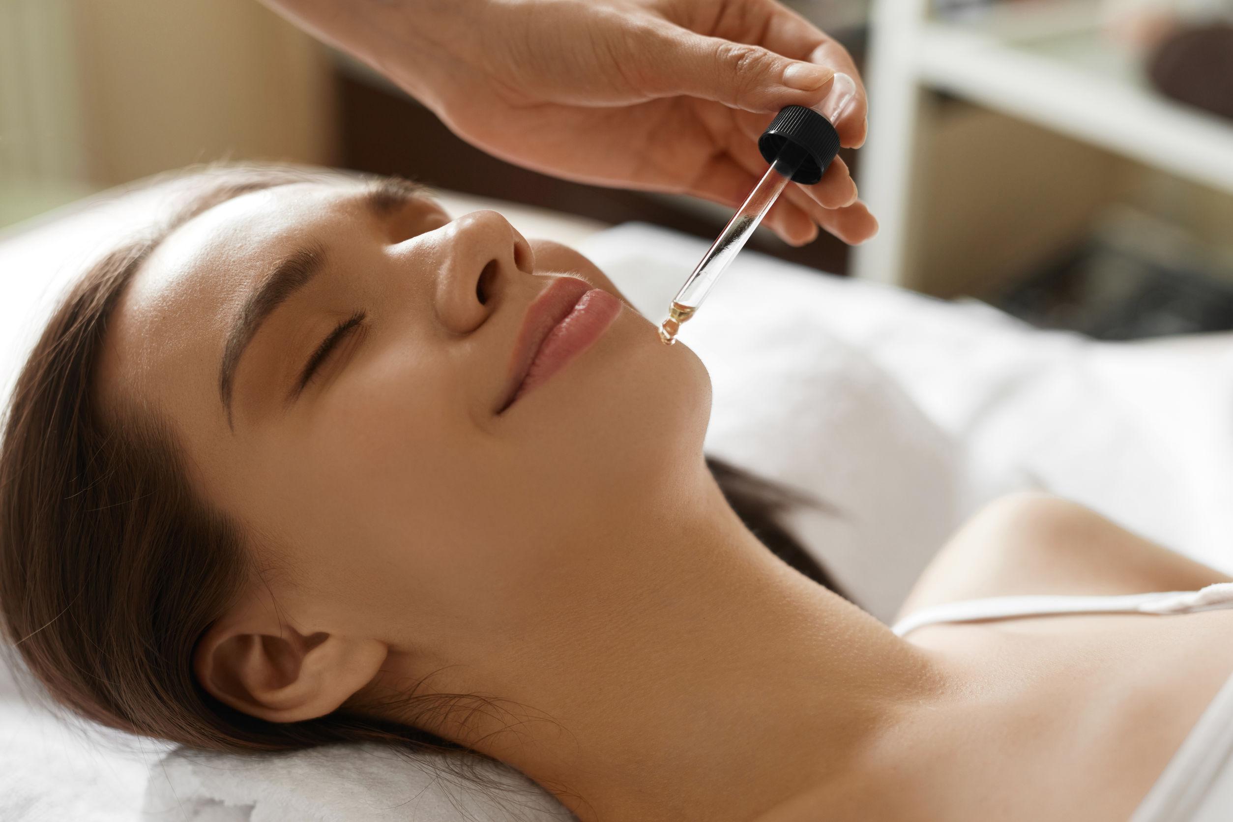 Primer plano de hermosa mujer sonriente recibiendo tratamiento con aceite de suero en salón de belleza.
