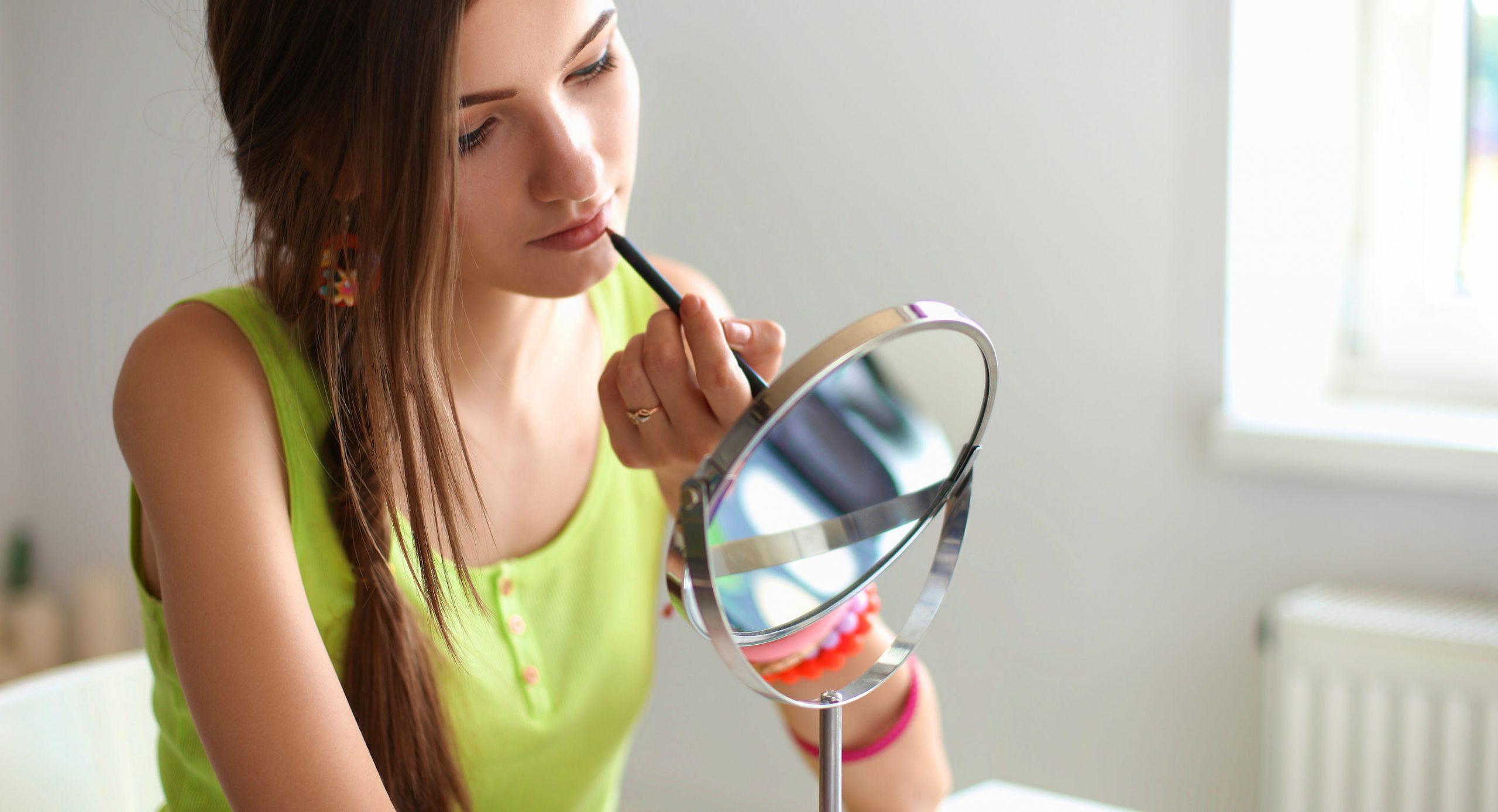chica arreglandose con espejo