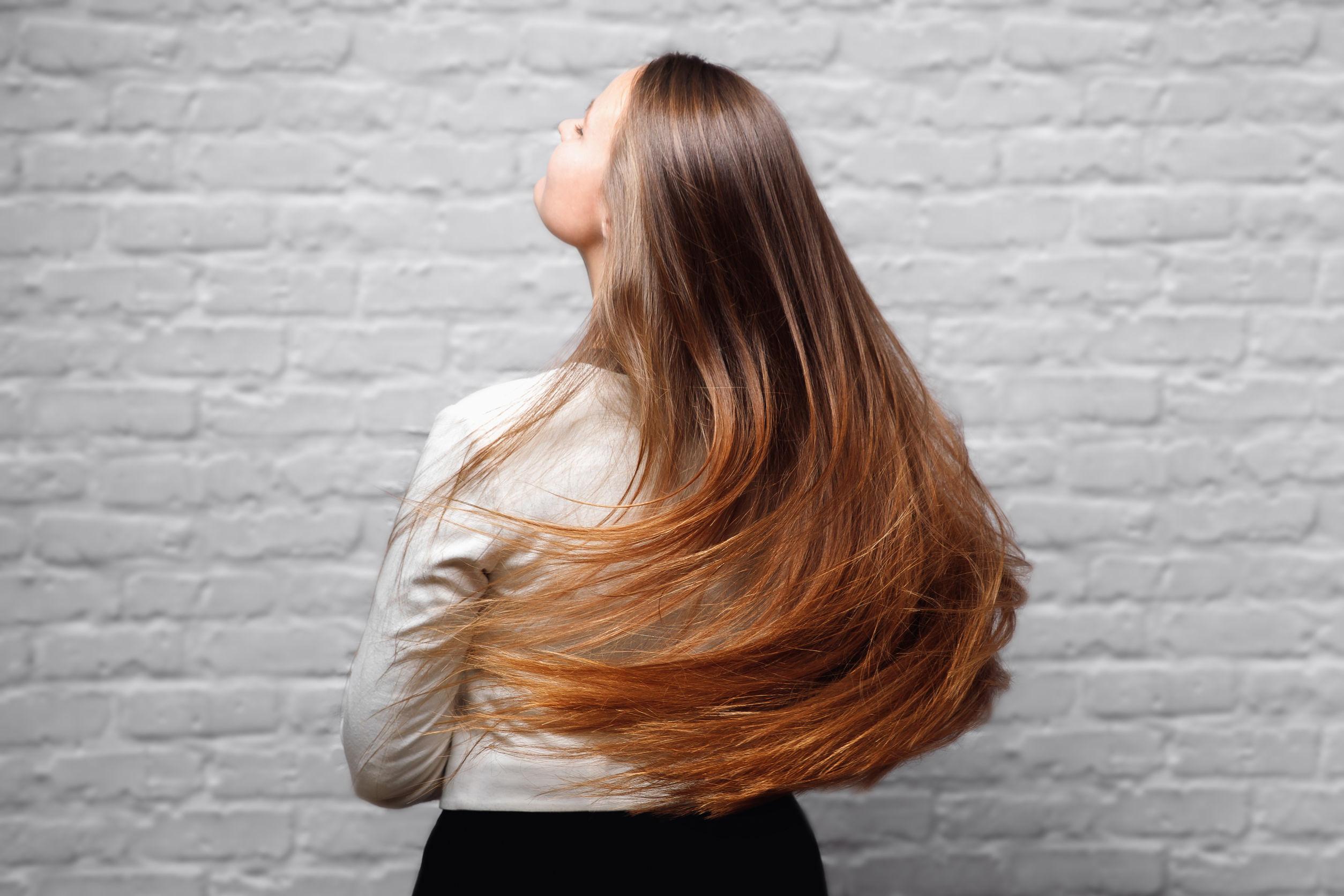 Mujer de cabello largo y castaño moviendolo sobre fondo de pared