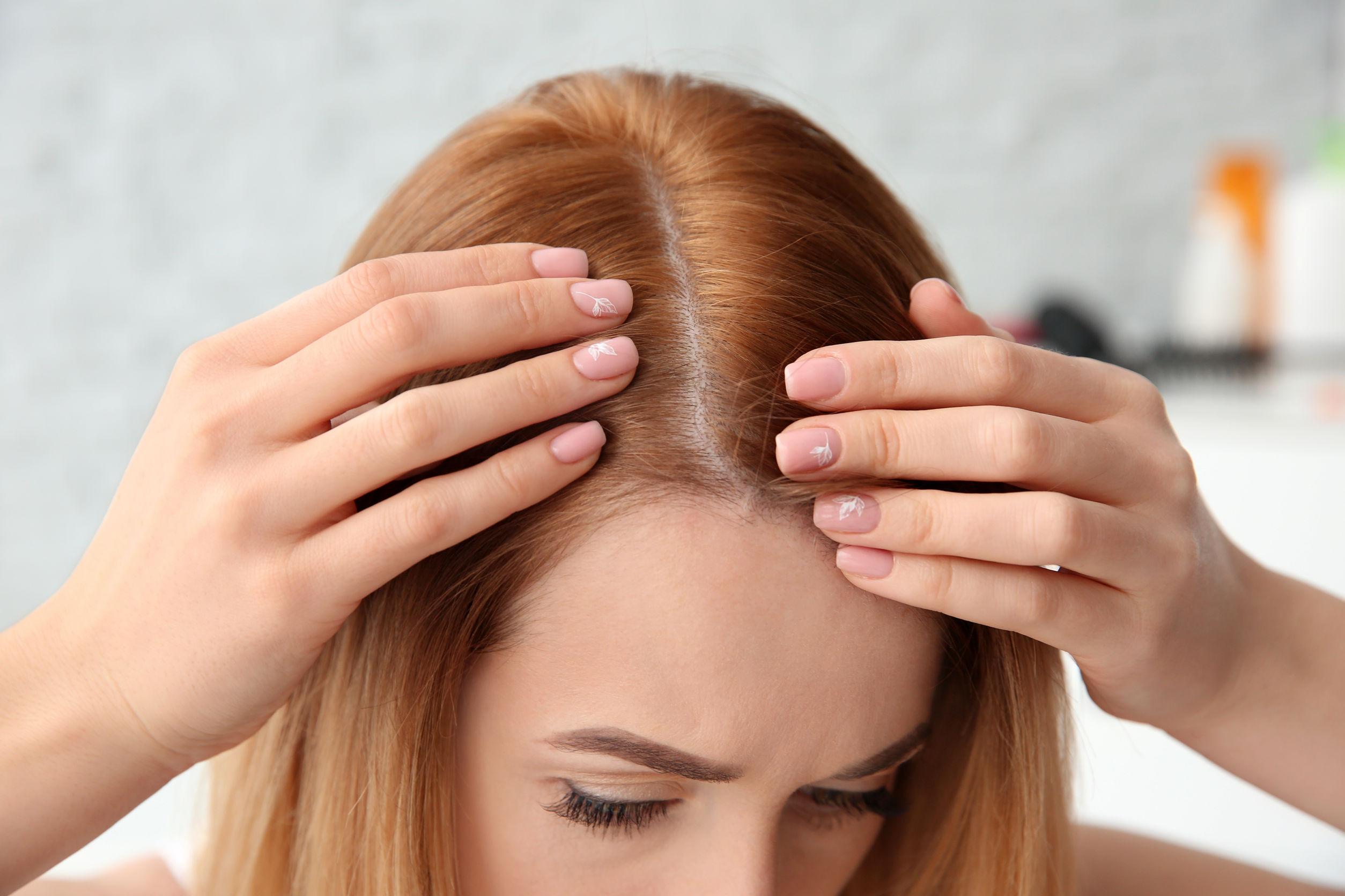Mujer joven feliz lavándose el cabello con champú, manos con espuma de cerca.