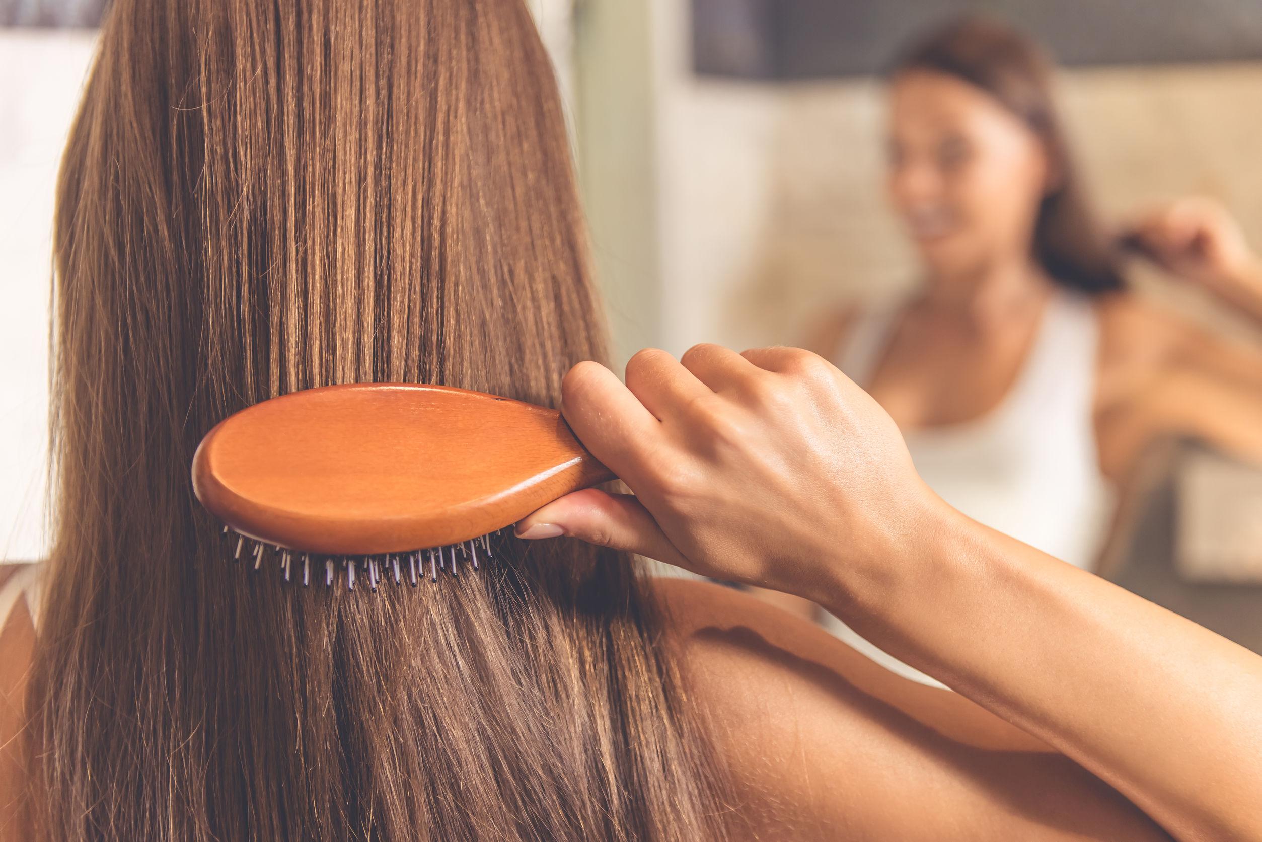 chica cepillandose su cabello