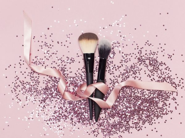 Two different Cosmetic makeup brushes with pink ribbon and holographic glitter confetti in the form of stars on pink background Flat lay top view copyspace Makeup accessories holiday birthday newyear.