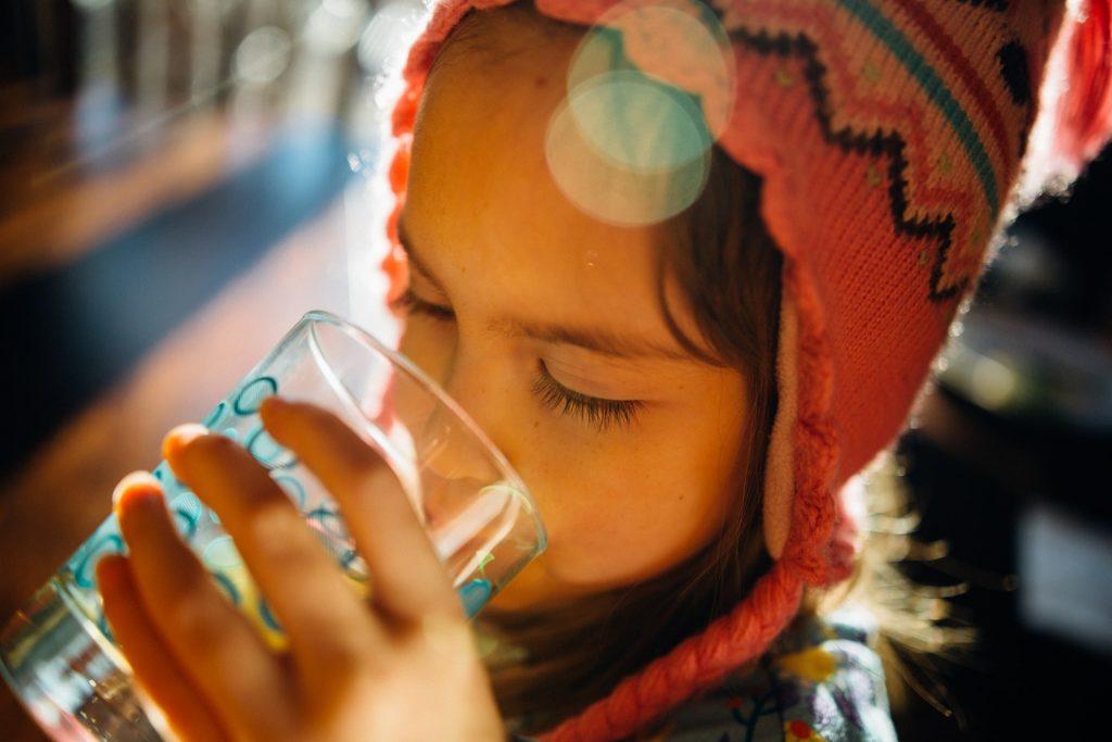 niña tomando agua purificada