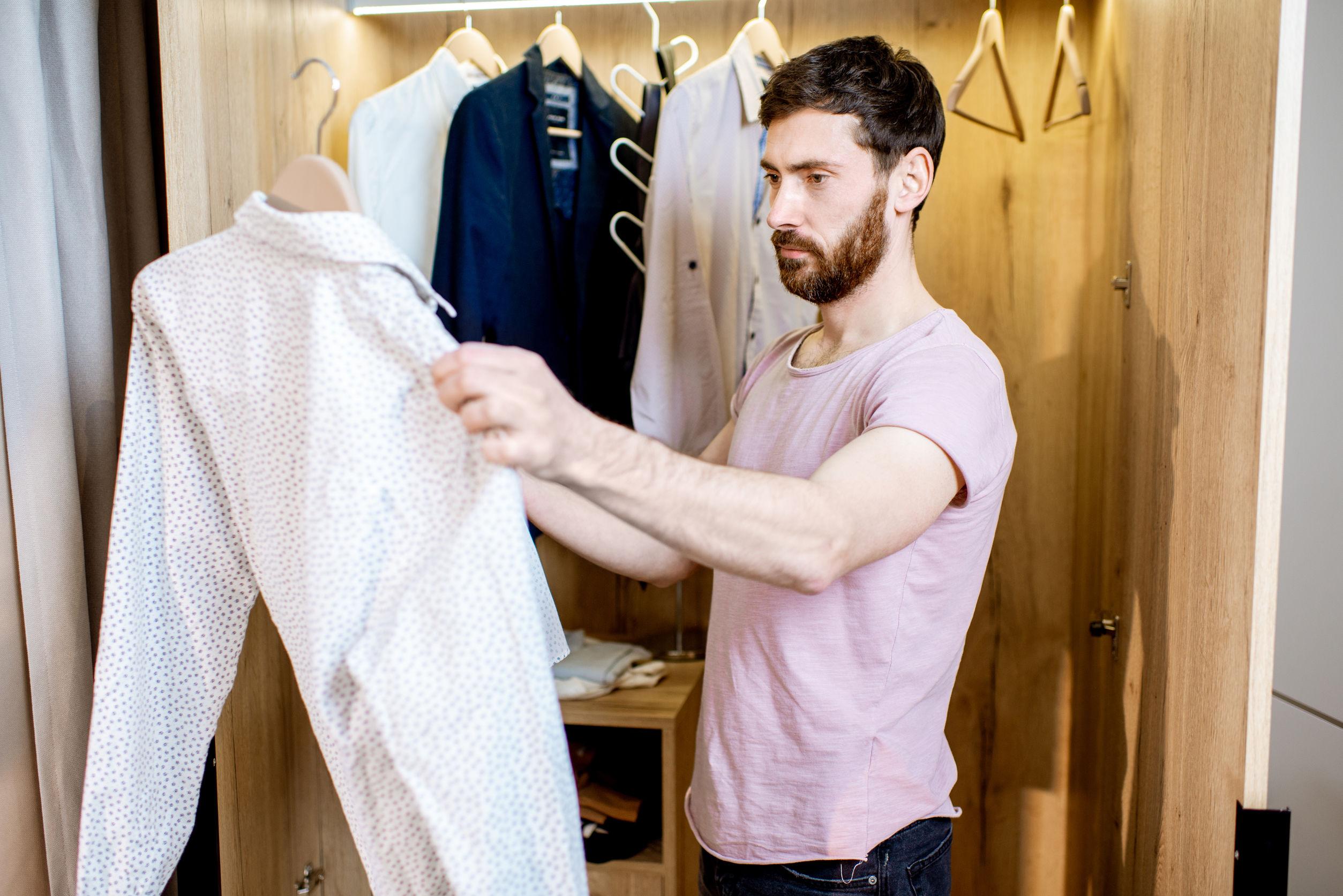 Hombre guapo eligiendo camisa para usar de pie en el armario en casa