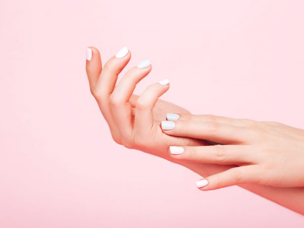 Tender hands with perfect blue and pink manicure on trendy pastel pink background. Place for text.