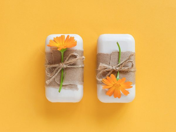 Handmade natural soap set decorated with craft paper, scourge and orange calendula flowers on yellow background. Organic cosmetics concept. Top view Flat lay Template for design.
